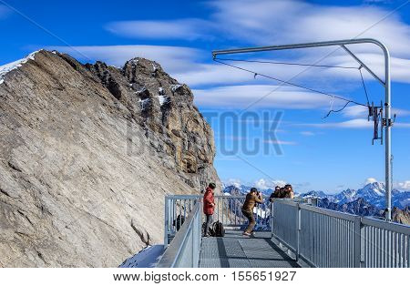 Mt. Titlis, Switzerland - 12 October, 2015: people taking pictures in the foreground, mountains in the background. Mount Titlis is a mountain of the Uri Alps located on the border between the Swiss cantons of Obwalden and Bern.