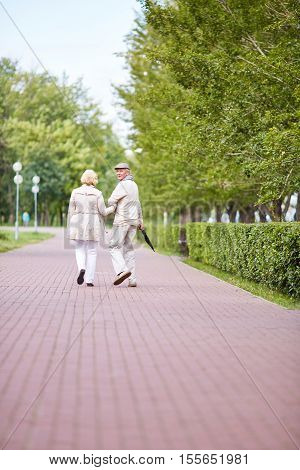 Senior couple walking away, man turning back and looking at camera over his shoulder