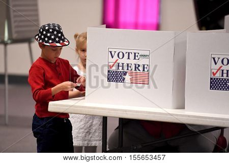 Saint Louis, MO - November 8, 2016: Children wait while relative exercises right to vote during Presidential elections in Saint Louis, Missouri