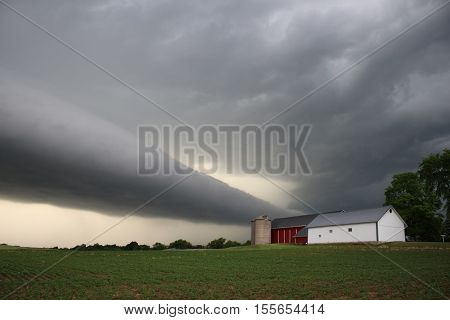 A eerie roll cloud approaches a small midwestern farm.