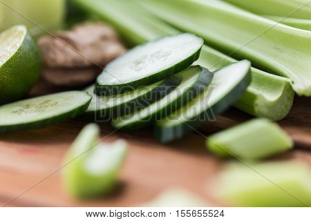healthy eating, food, dieting and vegetarian concept - close up of green celery stems and sliced cucumber on wood