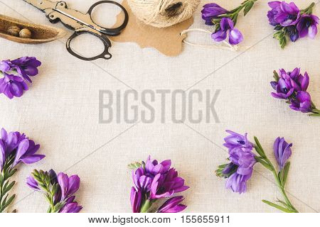 Purple flowers craft twine work on linen toning copy space background