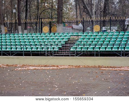 Outdoor theater in the park in the fall after the first snowfall. An amphitheater and places for the audience.