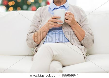 old age, holidays, drinks and people concept - close up of senior woman with cup of tea at home over christmas tree background