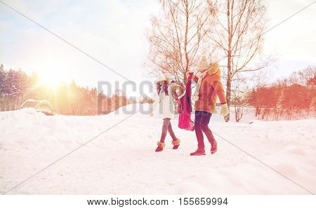 parenthood, fashion, season and people concept - happy family with child in winter clothes walking and having fun outdoors