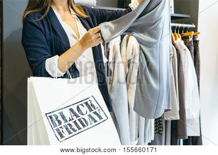 Close up of incognito woman looking at grey blouse while shopping on Black Friday. Cropped view. Copy space