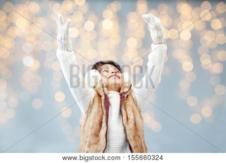 winter, christmas, people, happiness concept - happy little girl wearing earmuffs over holidays lights background