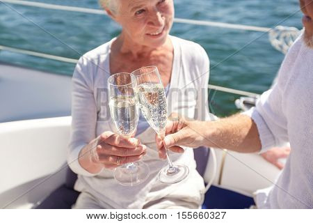 sailing, age, travel, holidays and people concept - close up of happy senior couple drinking champagne on sail boat or yacht deck floating in sea