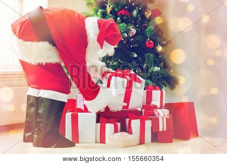 holidays, celebration and people concept - man in costume of santa claus putting present under christmas tree over lights
