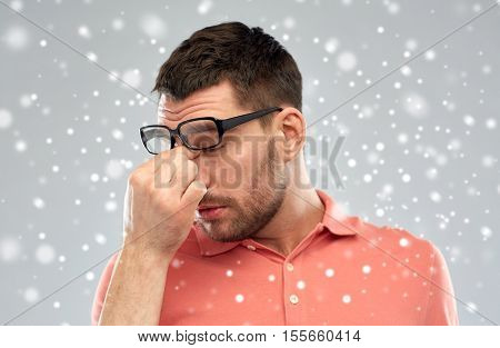 business, people, vision, winter and overwork concept - tired man with eyeglasses touching nose bridge over snow on gray background