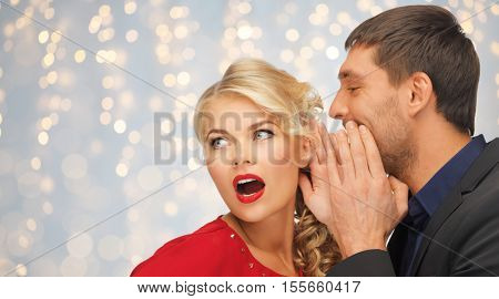 people, communication, christmas , holidays and information concept - close up of man and woman spreading gossip over holidays lights background