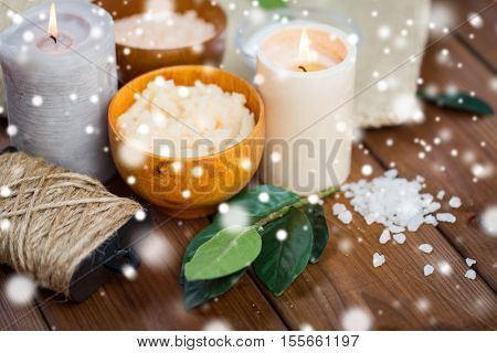 beauty, spa, therapy and natural cosmetics concept - body scrub, salt and candles on wood over snow