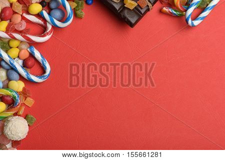 Red textured background with mix of colorful dragee with raisins or peanuts inside marmalade or jelly candies striped caramel candies coconut candy and chocolate bar with thread copy space
