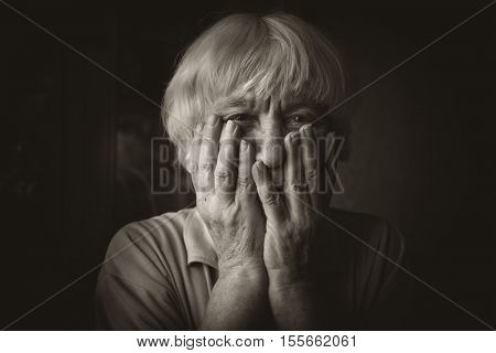 Vintage style monochrome photo. Sad elderly woman. She covered her face with her hands.