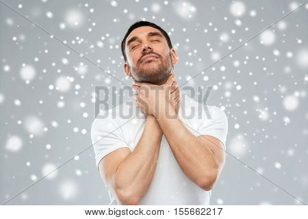 suicide, death, winter, christmas and people concept - young man choking himself by hands over snow on gray background