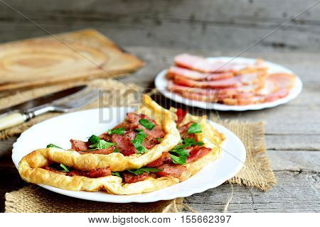 Homemade bacon omelette recipe. Beautiful omelette stuffed with fried bacon and fresh parsley on a plate, bacon slices, fork, knife, cutting board, on old wooden background. Delicious breakfast recipe