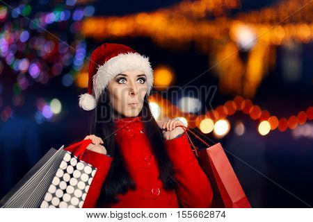 Surprised Christmas Woman With Shopping Bags Looking for Presents in Xmas Fair