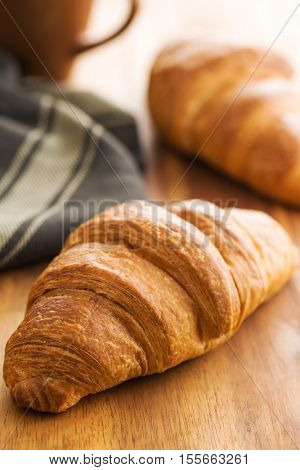 Tasty buttery croissant on kitchen table.