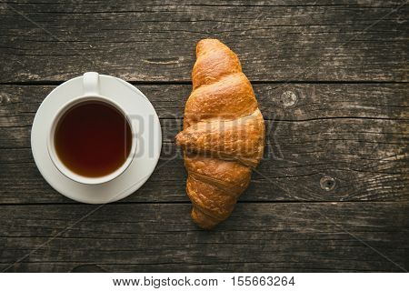 Tasty buttery croissant and cup of tea. Top view.