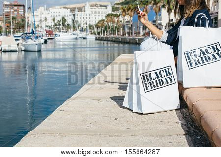 Side view of incognito woman using smartphone next to Black Friday shopping bags. Copy space