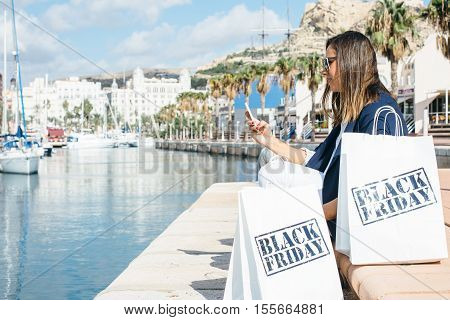 Woman sitting on sea front and using cell phone after Black Friday shopping. Copy space