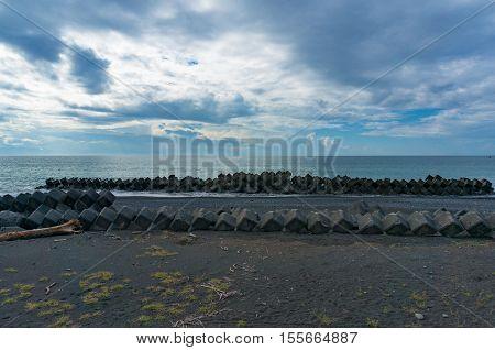 Suruga bay coastline with dark volcanic sand concrete breakwater and driftwood. Shizuoka Japan