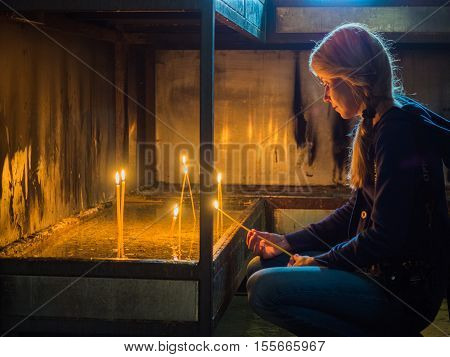 Picture of the girl with long fair hair lighting wax candles in a church. Female discovers spiritual order in a church. The girl looking to the wax candle's flame.