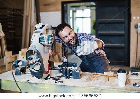 Carpenter taking a selfie with miter saw at his work place.