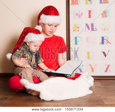 Boys in Santa hats reading a Christmas book. Big brother reading to his little baby brother in the nursery.