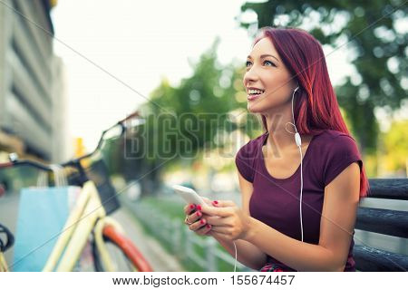 Red-haired girl sitting on the bench and use the phone next to her have been parked bicycle