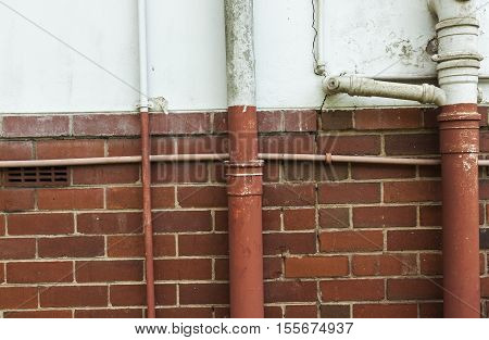 Neglected Vintage old plumbing pipes on cracked blue and red brick wall background