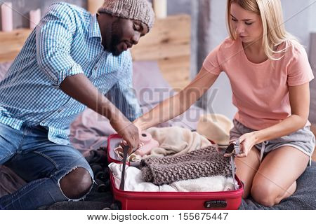 Be ready. Delighted international young couple packing their suitcase and preparing for a journey while spending time in bedroom.
