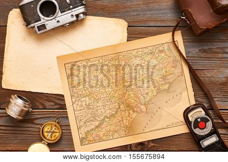 Vintage old 35mm cameras, lenses and light meter on wooden background with antique XIX century map
