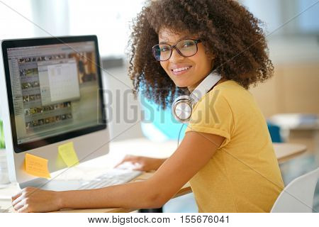 Cheerful mixed-race girl designing in office on desktop computer