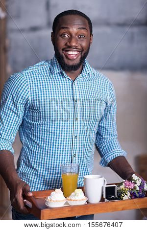 It is coming. African young overjoyed man preparing for marriage proposal while holding a tray with breakfast and the ring and smiling.