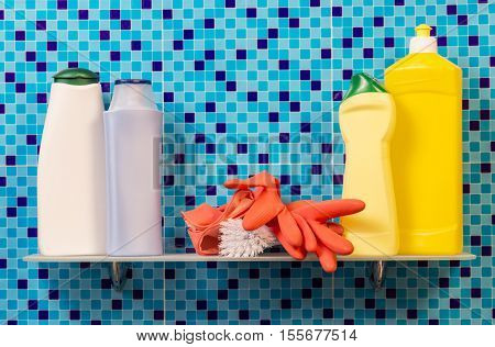 Shelf with bottles of detergent, rubber gloves and brush on an abstract blue background.