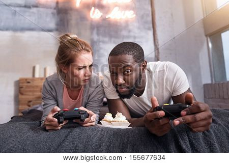 Funny game. Overjoyed delighted international couple eating cupcakes and playing video games why enjoying weekends.