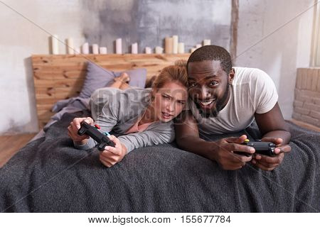 Sweet family times. Overjoyed young international couple enjoying video games and using console while lying in bed.