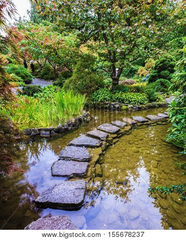 World masterpiece of landscape design.  Decorative private garden in western Canada - Butchart Gardens. The track of the stones in the Japanese part of the garden