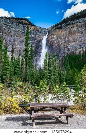 Comfortable wooden table and benches for a picnic. Waterfall Takakkaw in Yoho National Park in the Rocky Mountains