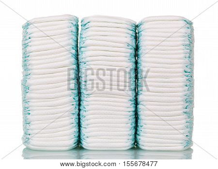 Three stacks of disposable diapers isolated on white background.