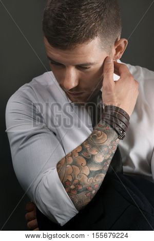 Young tattooed man posing on dark background