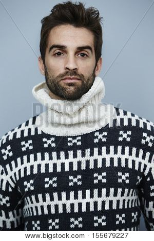 Serious man in knitwear posing for camera
