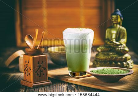 Cup of green tea matcha latte with matcha powder