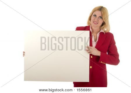 Happy Female Executive In Red Holding Blank Sign