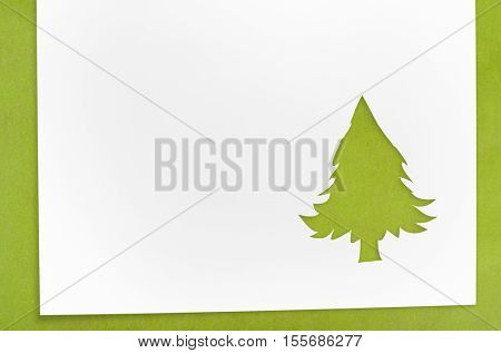 Cut paper in christmas tree shape for christmas card or new year background on green table