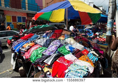 Port of spain Trinidad and Tobago - November 28 2015: colorful clothes displayed for sale on local south market outdoors on sunny summer day on streetscape background