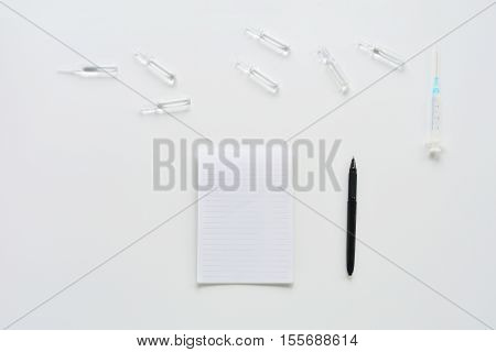 Medical composition with syringe, ampoules and notebook on white background. Top view of doctor workplace. Flat lay mock up.