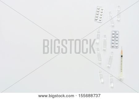 Medical composition with syringe, pills and ampules on white background. Top view of doctor workplace. Vertical flat lay mock up.