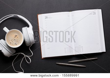 Office leather desk table with notepad, headphones and coffee. Top view with copy space